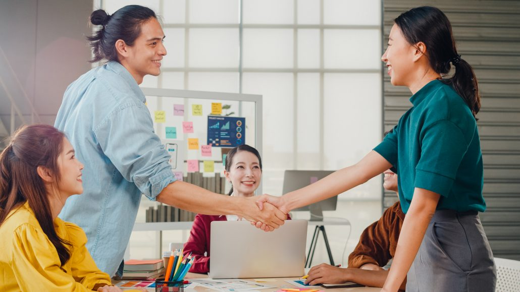 multiracial group young creative people smart casual wear discussing business shaking hands together smiling while standing modern office partner cooperation coworker teamwork concept
